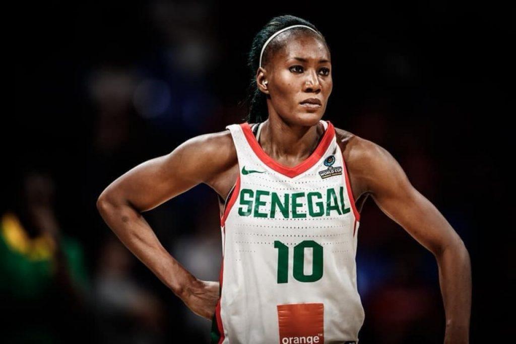 La basketteuse Astou Traoré porte un maillot du Sénégalaise et se tient debout en plein match de basket