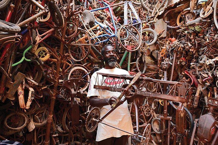L'artiste Meissa Fall au milieu de son oeuvre d'art crée à partir de vélos recyclés