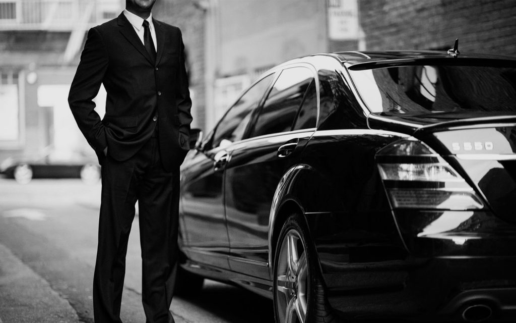 Un chauffeur de la compagnie de VTC Uber qui attend un client devant sa voiture berline