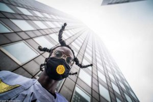 Un garcon en bas d'un immeuble avec un masque devant la bouche festival