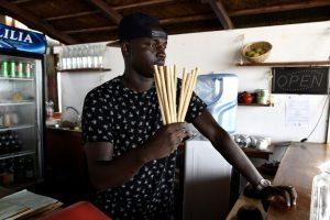 Babacar Thiaw, le gérant du restaurant Copacabana à Dakar tenant des paille en bois dans sa main, plastique