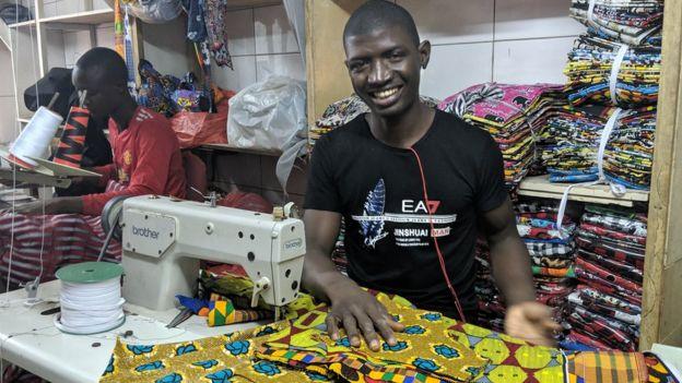 Un homme en train de coudre avec une machine dans la fabrique artisanale de Sandaga à Dakar
