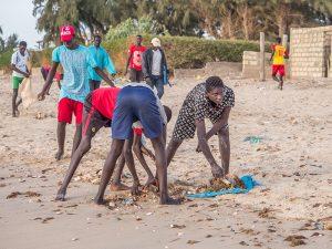 Des enfants ramassent des plastiques sur une plage sénégalaise
