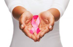 Une femme tenant dans la main un ruban rose pour le cancer du sain et du col de l'utérus
