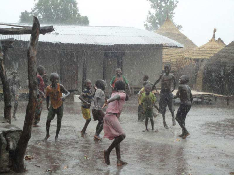 Des enfants d'un petit village sénégalais jouent sous la pluie battante