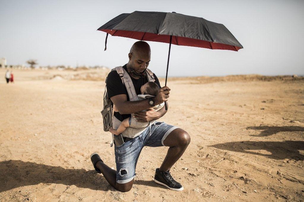Au Sénégal, en écho au calvaire de George Floyd, Alexis Tangana, son bébé métisse dans les bras, s'agenouille sur le site du mémorial de Gorée, aux victimes de la traite © AFP / John Wessels